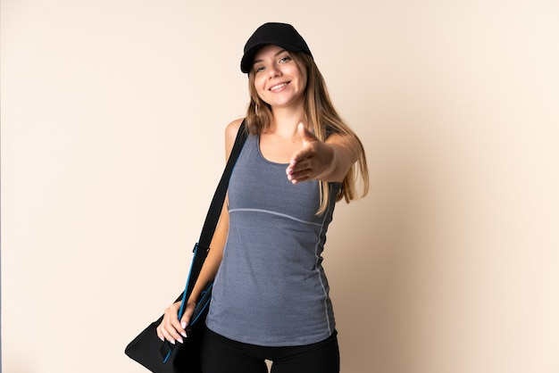 Litauische junge sportfrau, die eine sporttasche lokalisiert auf beigem hintergrund hält händeschütteln für das schließen eines guten geschäfts hält