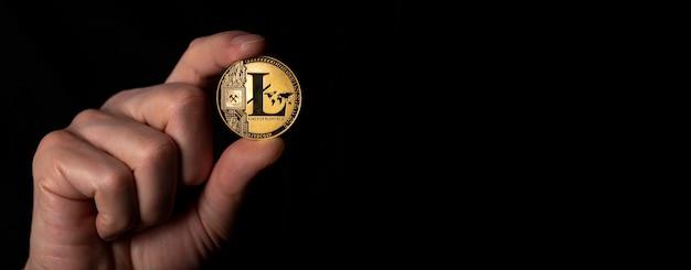 Litecoin goldene münze in der männlichen hand über schwarzem hintergrund. banner mit platz für text.
