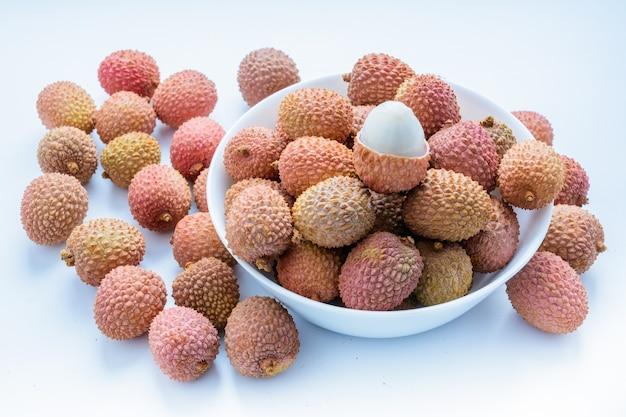 Litschi (lee-chee; litchi chinensis) ist das einzige mitglied der gattung litchi in der familie der seifenbaumgewächse, sapindaceae. lychee ist auf einem teller auf weißem hintergrund. reife litschi ohne schale. tropische frucht.