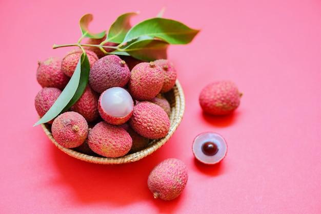 Litschi-scheibe geschält auf rotem rosa hintergrund. frische litschi mit grünen blättern ernte im korb vom baum tropischen fruchtsommer in thailand