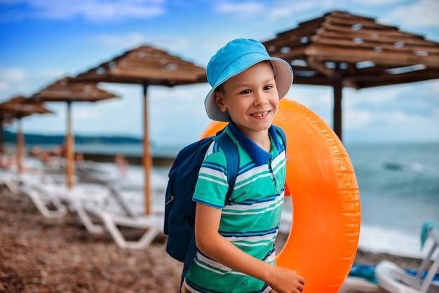 Little boy 6 jahre alt in einem hut mit einem aufblasbaren orangefarbenen kreis läuft