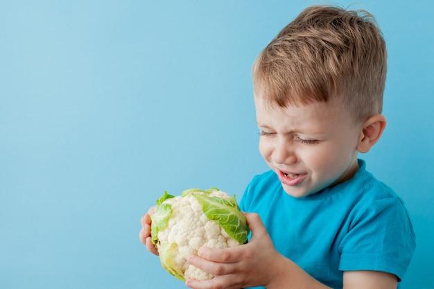 Little boy, das brokkoli in seinen händen auf blauem hintergrund hält