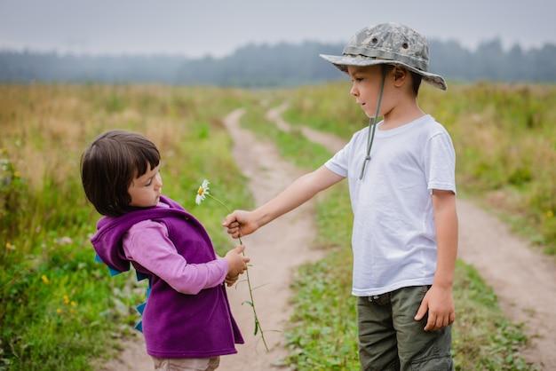 Little boy geschenk blüht sein freund mädchen.