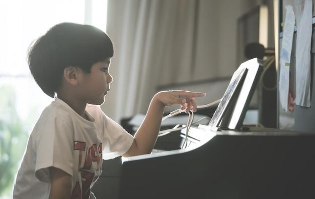 Little boy spielt zu hause mit klavier und music tablet