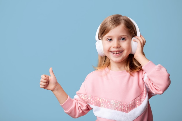 Little girl blogger influencer zeichnet videos aus dem blog auf einem smartphone auf, kommuniziert mit abonnenten, setzt likes, hört musik mit kopfhörern und lernt ferngesteuert an einer isolierten wand.