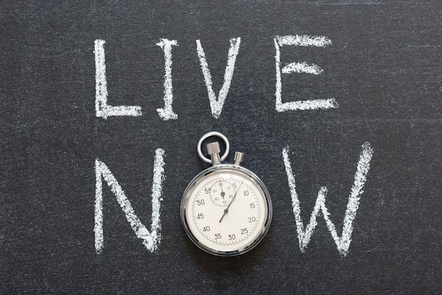 Live now konzept handschriftlich auf tafel mit vintage-präzisions-stoppuhr anstelle von o