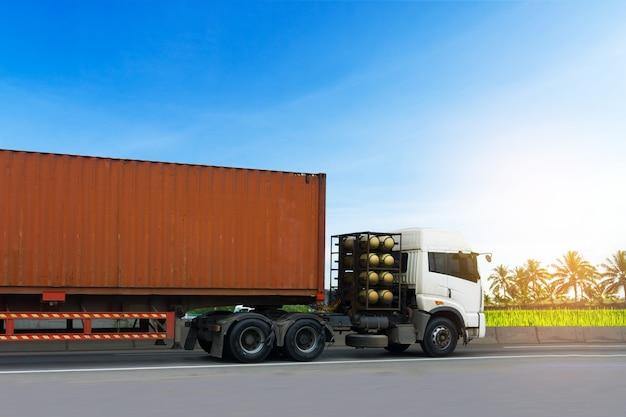 Lkw auf landstraße straße mit rotem behälter, import, logistischer industrietransport des exports