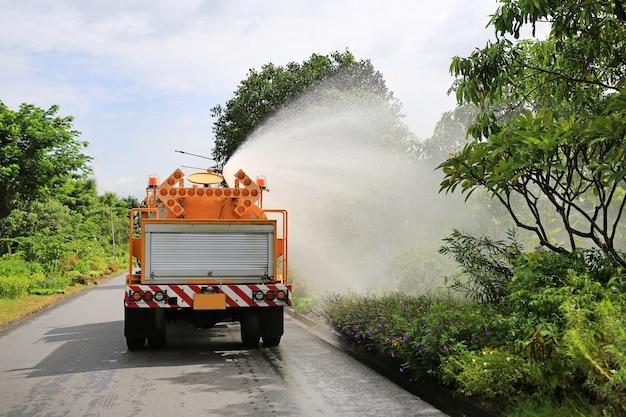Lkw, der einen baum durch spraywasser im parkgarten wässert.
