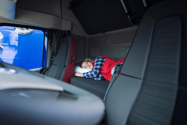Lkw-fahrer, der auf bett innerhalb des innenraums der lkw-kabine schläft