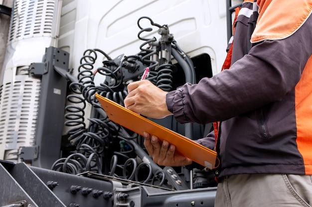 Lkw-fahrer hält zwischenablage und prüft die checkliste für die wartung von sicherheitsfahrzeugen des sattelschleppers