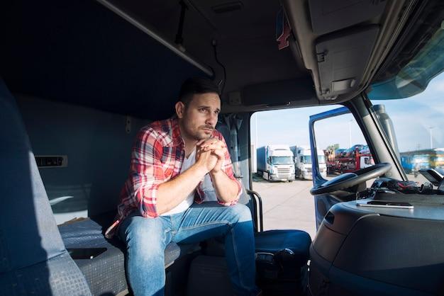 Lkw-fahrer sitzt in seiner kabine und denkt an seine familie