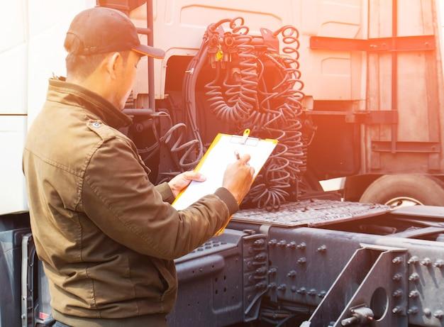 Lkw-fahrer überprüft die checkliste für die lkw-sicherheitswartung