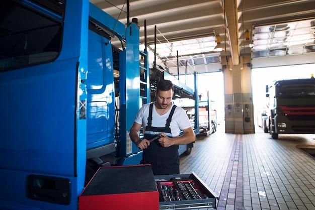 Lkw-mechaniker, der lkw-fahrzeug in der werkstatt wartet