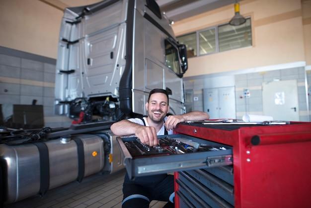Lkw-mechaniker und servicemann, der werkzeuge für die fahrzeugwartung auswählt