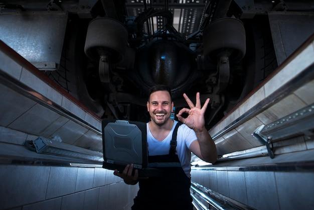 Lkw-servicemann mit mit laptop-diagnosewerkzeugen, die okay gestenzeichen zeigen