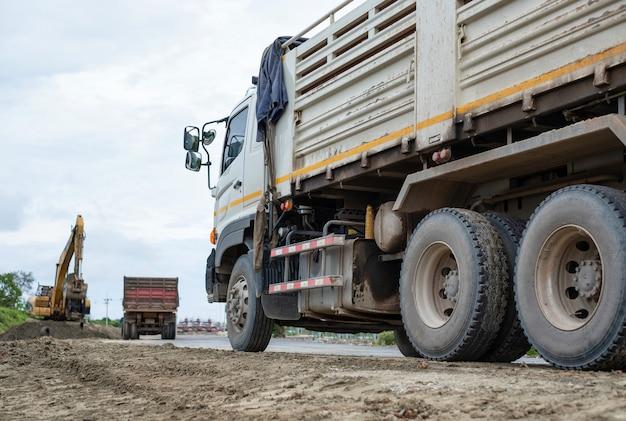 Lkw wartet einen löffelbagger, um boden auf seine müllkippe zu füllen