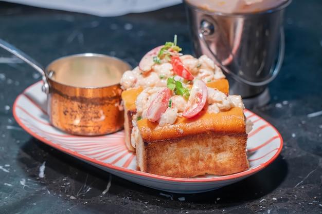Lobster roll.fresh maine lobster gekocht, gemischt mit mayo, sellerie, schnittlauch, serviert in geröstetem heldenbrötchen mit knusprigem salat und gezogener butter.
