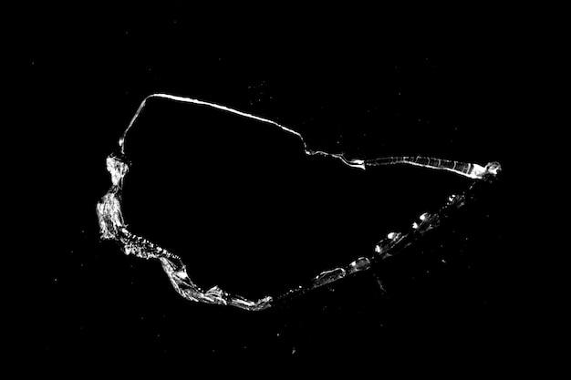 Loch im glas mit rissen auf schwarzem hintergrund isoliert. textur für design