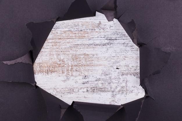 Loch im schwarzen papier. zerrissen. weißer hölzerner hintergrund. abstrakter hintergrund.