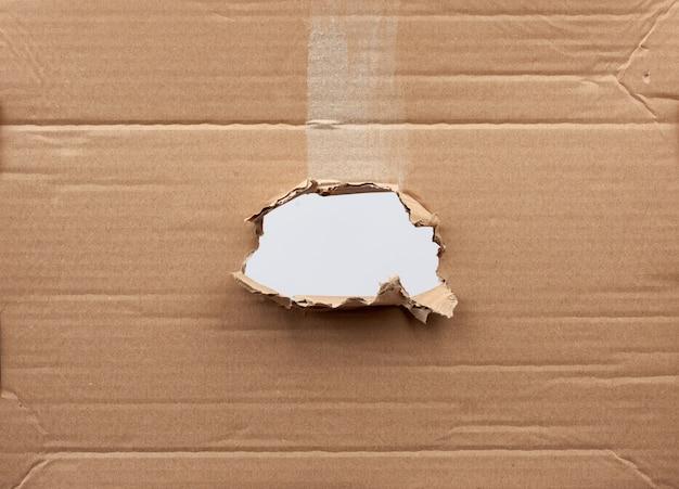 Loch in braunem kartonpapier mit zerrissenen und gebogenen kanten