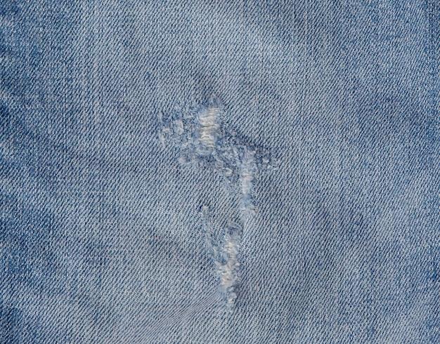 Loch und fäden auf jeans. zerrissener zerstörter heftiger blue jeanshintergrund. schließen sie herauf blaue baumwollstoffbeschaffenheit