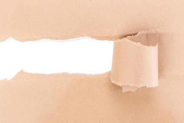 Loch zerrissen in braunes papier auf weißem hintergrund.