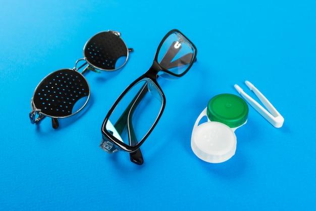 Lochbrillengläser, linsen mit behälter und gläser zum sehen. medizinisches konzept. eine reihe von zubehör für den anblick. ansicht von oben