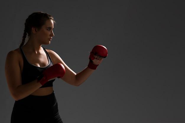 Lochen mit boxhandschuhen und dunklem hintergrund