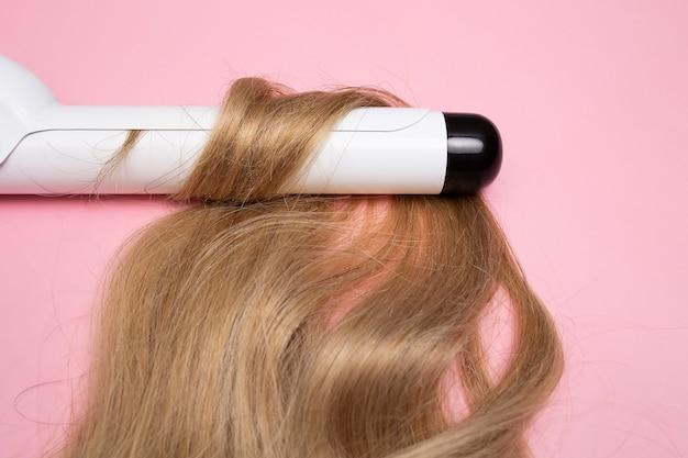 Lockenblondes haar auf einem lockenstab mit großem durchmesser auf einem rosa hintergrund locken pflege-haarstyling