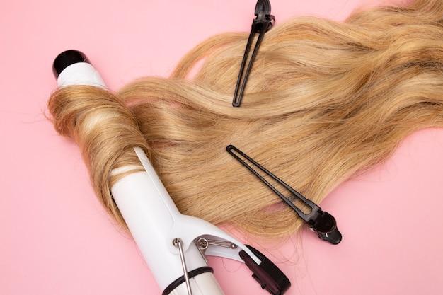 Lockenblondes haar auf einem lockenstab mit großem durchmesser auf einem rosa hintergrund locken pflegehaar, das schwarze clips stylt