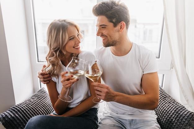 Lockige blonde frau, die freund beim trinken von champagner betrachtet. gut gelauntes paar, das feiertage feiert.