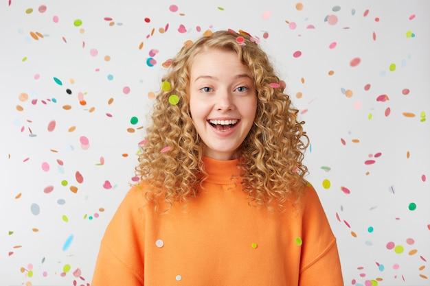 Lockige blondine im orangefarbenen pullover genießt den moment des lebens unter konfetti-regen