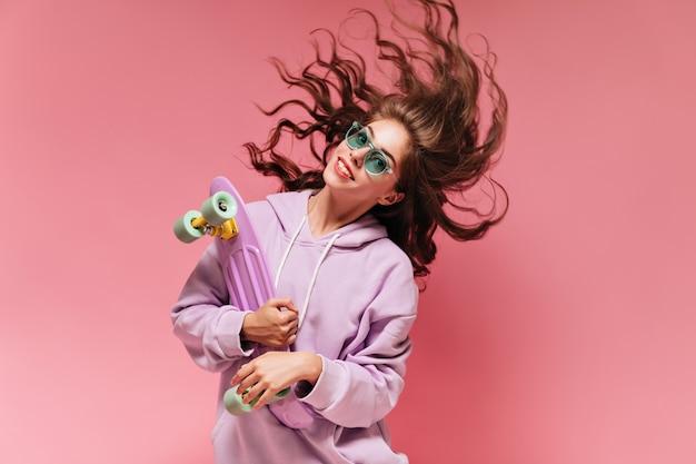 Lockige brünette frau in lila übergroßem hoodie spielt haare