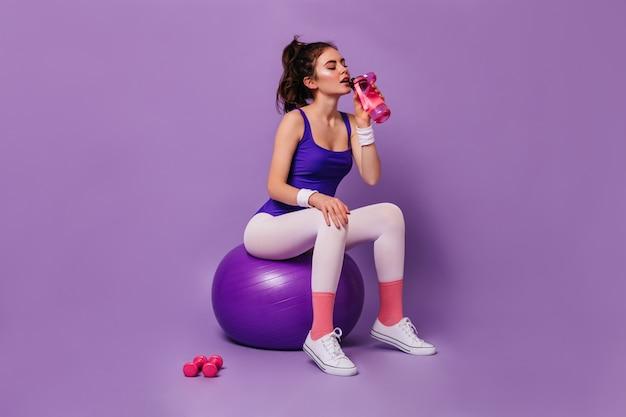 Lockige dunkelhaarige frau in sportbekleidung im stil der 80er jahre sitzt auf fitball und trinkt wasser aus der rosa flasche
