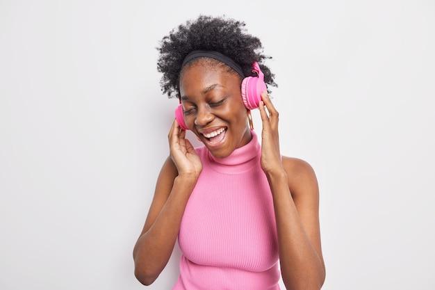 Lockige dunkelhäutige frau mit dunkler haut vergisst alle probleme, da sie coole musik über kopfhörer genießt, fühlt sich sehr glücklich und hält die augen geschlossen
