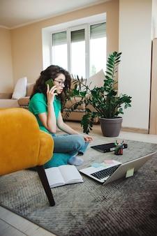 Lockige frau auf dem boden mit laptop, während sie hausaufgaben macht freiberufliche freiberufliche arbeit