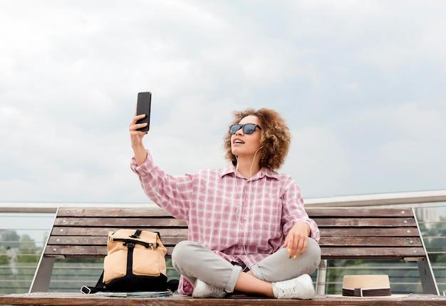 Lockige frau, die ein selfie auf einer bank nimmt