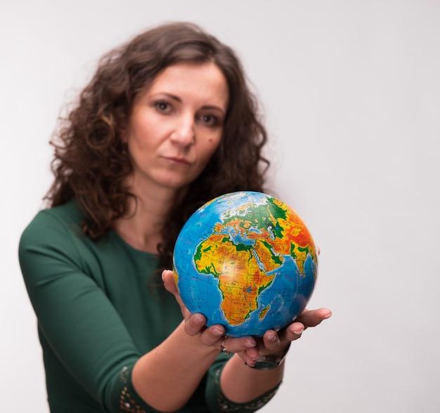 Lockige frau, die einen globus auf einem grauen hintergrund hält