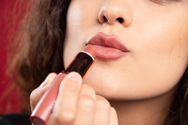 Lockige frau, die lippenstift anwendet.
