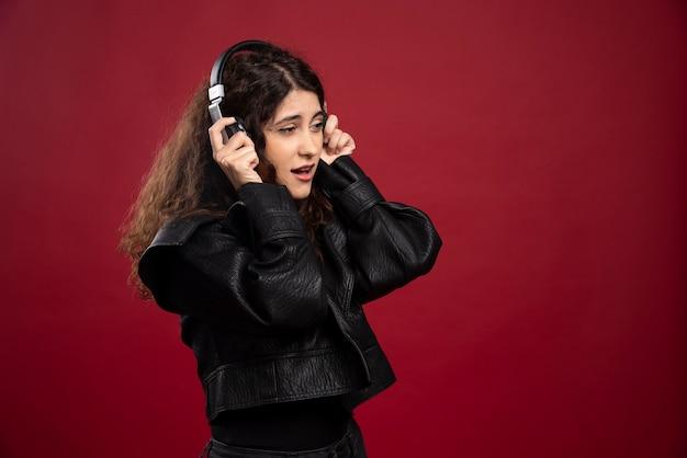 Lockige frau, die musik hört und singt.