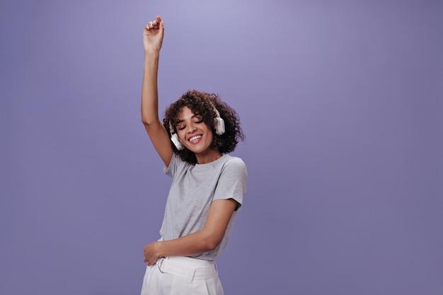 Lockige frau im grauen t-shirt und kopfhörer tanzt auf lila wand