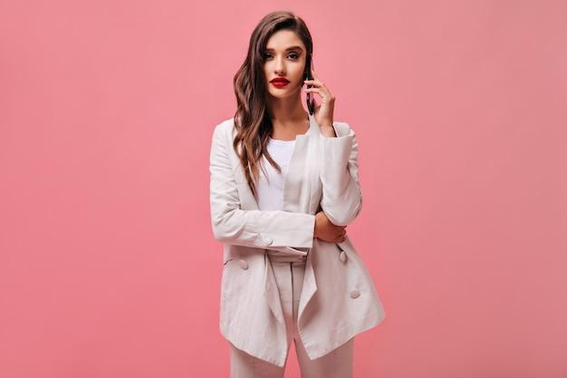 Lockige frau im weißen anzug spricht am telefon. stilvolle dame mit roten lippen im hellen modischen outfit auf rosa lokalisiertem hintergrund.