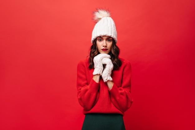 Lockige frau in rotem pullover, strickmütze und fäustlingen sieht vorne aus