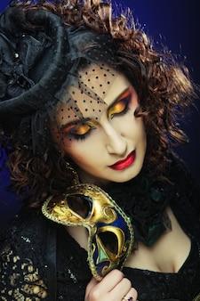 Lockige frau mit maske. karnevalsgesicht.