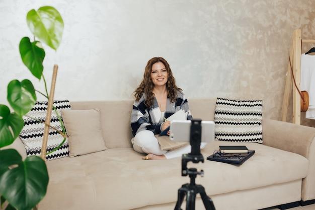 Lockige frau sitzt auf einem sofa mit einem smartphone auf einem stativ und filmt sich selbst