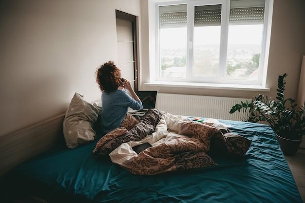 Lockige geschäftsfrau, die im schlafzimmer am telefon spricht, während sie einen laptop hält