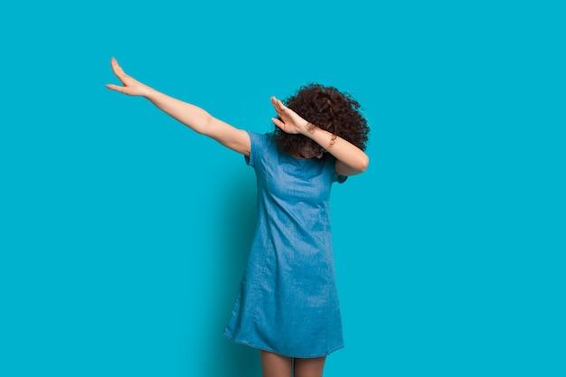 Lockige haarige kaukasische dame, die in einem schönen kleid auf blauem hintergrund tupft