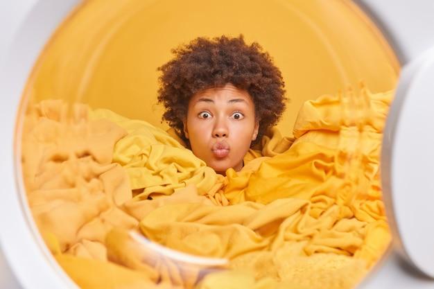 Lockige, hart arbeitende hausfrau, die in einem haufen wäsche ertrunken ist, hält die lippen gefaltet, sieht überraschend auf die vorderen posen aus der waschmaschine aus und wäscht?