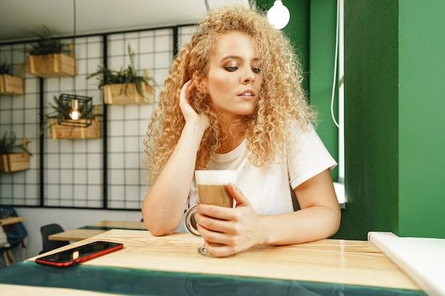 Lockige junge frau, die am tisch im kaffeehaus sitzt und sich mit tasse kaffee entspannt