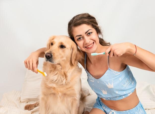 Lockige junge frau im pyjama, die bereit macht, goldene retrieverzähne zu hause zu putzen